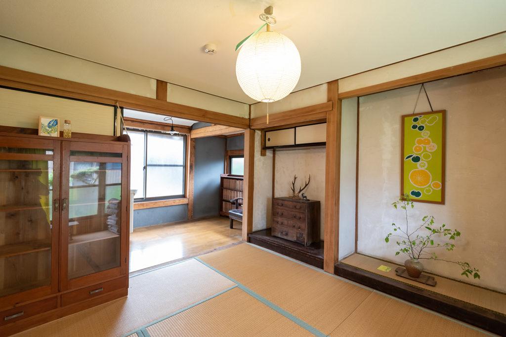 写真:ゆずの形をした照明と床の間のある和室。入り口横には箪笥が置いてある。