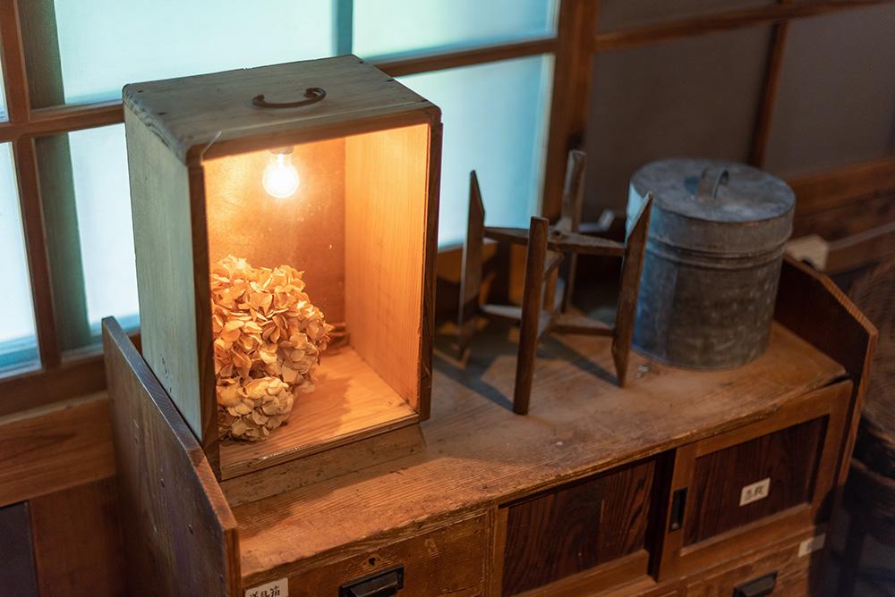写真:木箱に入った紫陽花のドライフラワーと電球のオブジェ。隣に糸巻きやブリキの缶が置いてある。