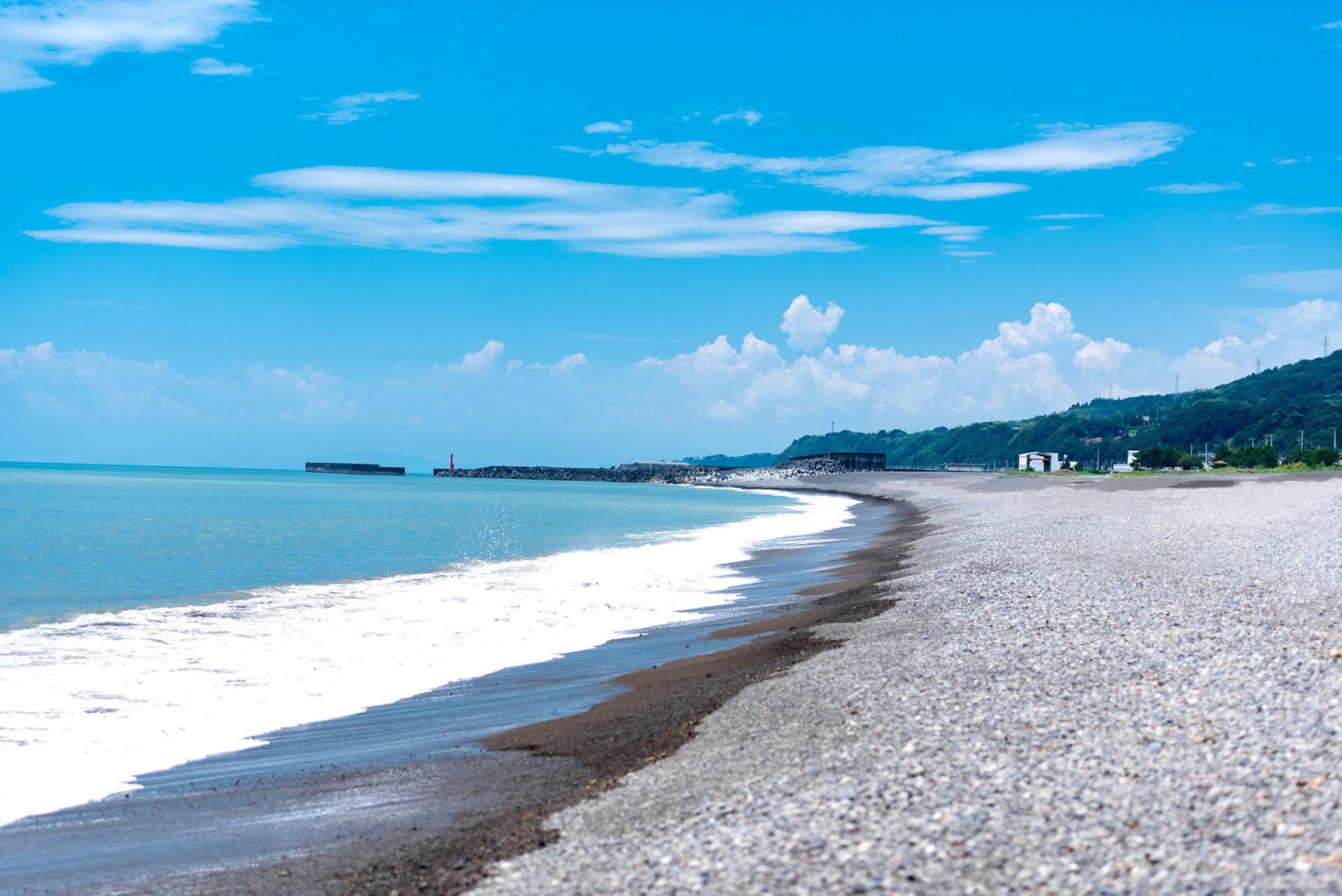 写真:波が打ち寄せる浜辺。青空と青い海。