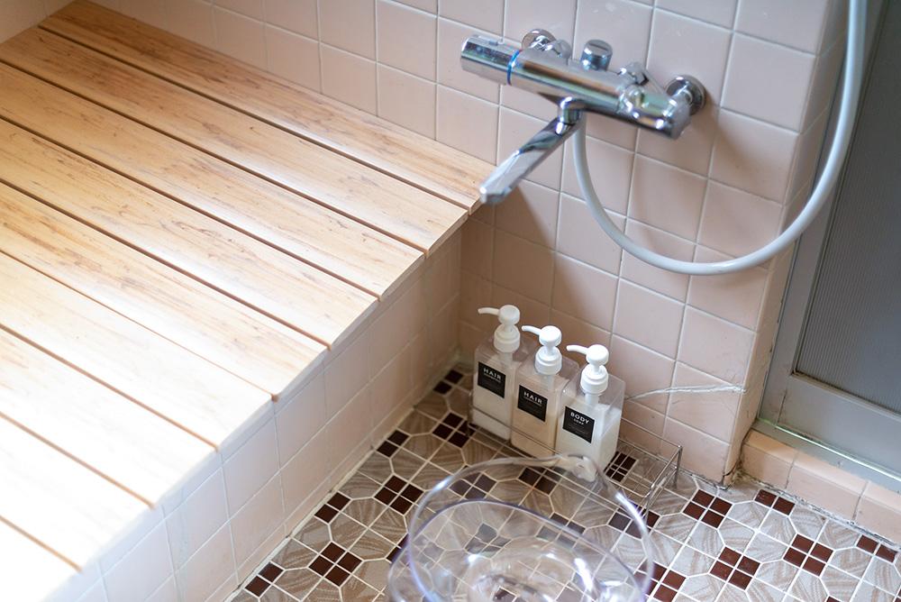 写真:タイルがレトロなお風呂場。浴槽には木の蓋がしてある。