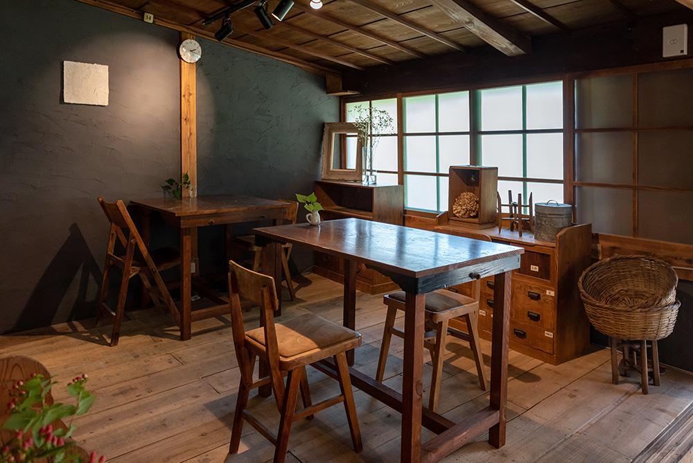 写真:2つの机があるカフェスペース。床は板張りで、壁はダークグレー。すりガラスの窓辺には雑貨が並んでいる。