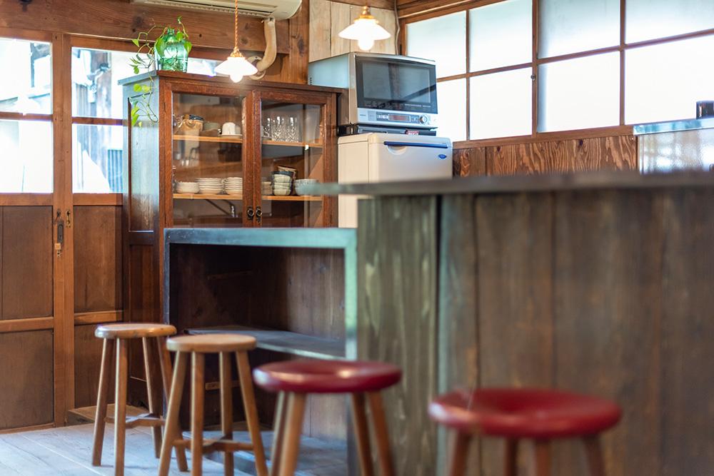 写真:キッチンカウンターと4つの丸椅子。奥には食器棚や冷蔵庫、電子レンジが置いてある。