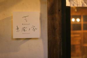 写真:入り口のサイン。漆喰の白壁に正方形のロゴ入りプレートが掛かっている