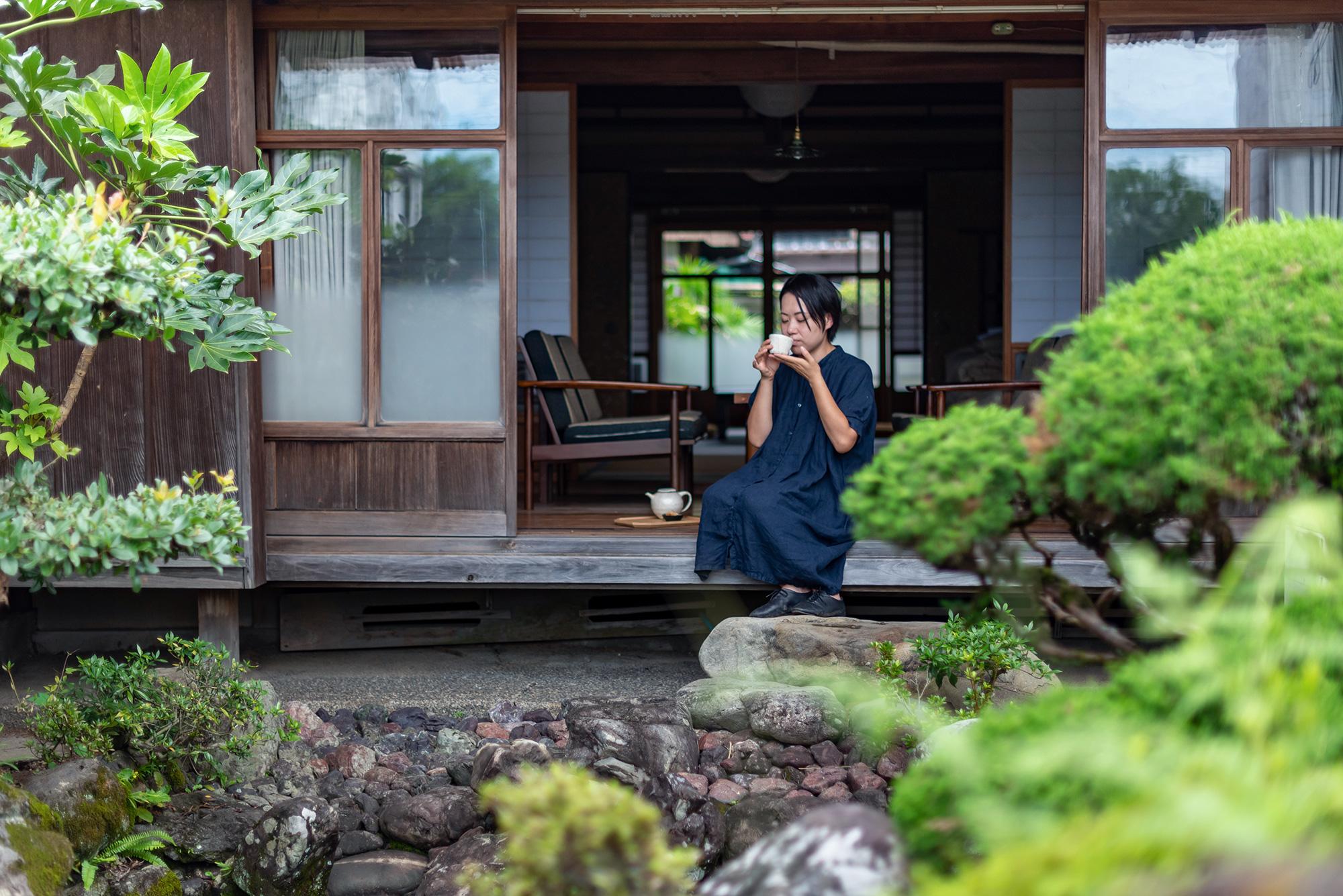 写真:縁側に腰掛けてお茶を飲む女性を庭から見た所。
