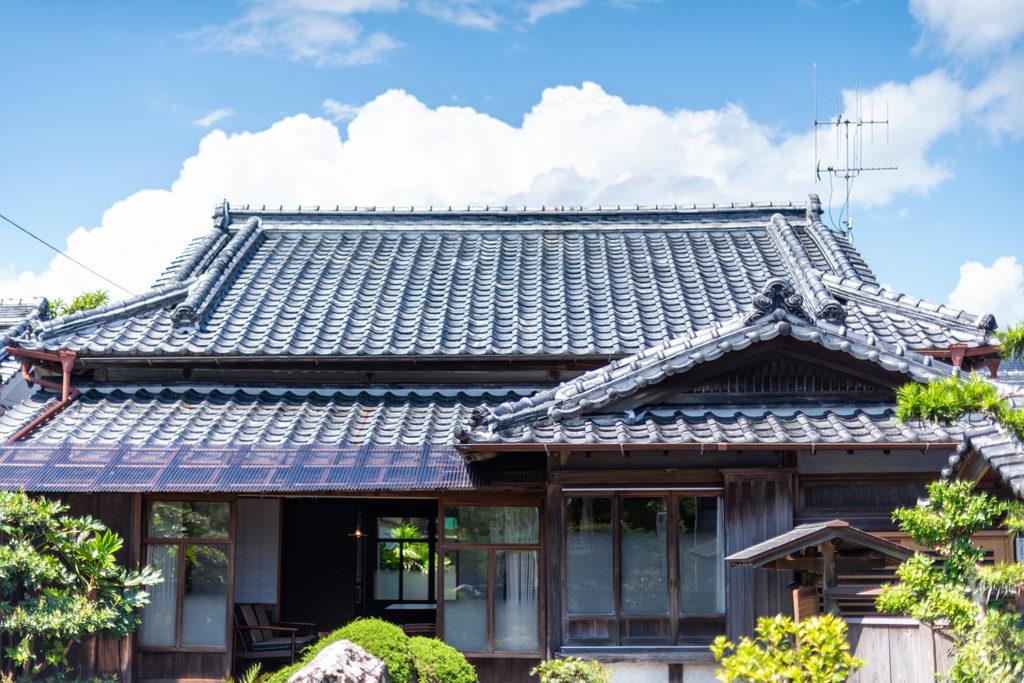 写真:古民家の外観。立派な瓦屋根と縁側とがある。青空と雲。