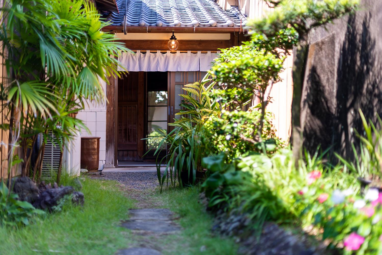 写真:古民家の玄関へと続く小道。玄関には短い白いのれんがかかっている。