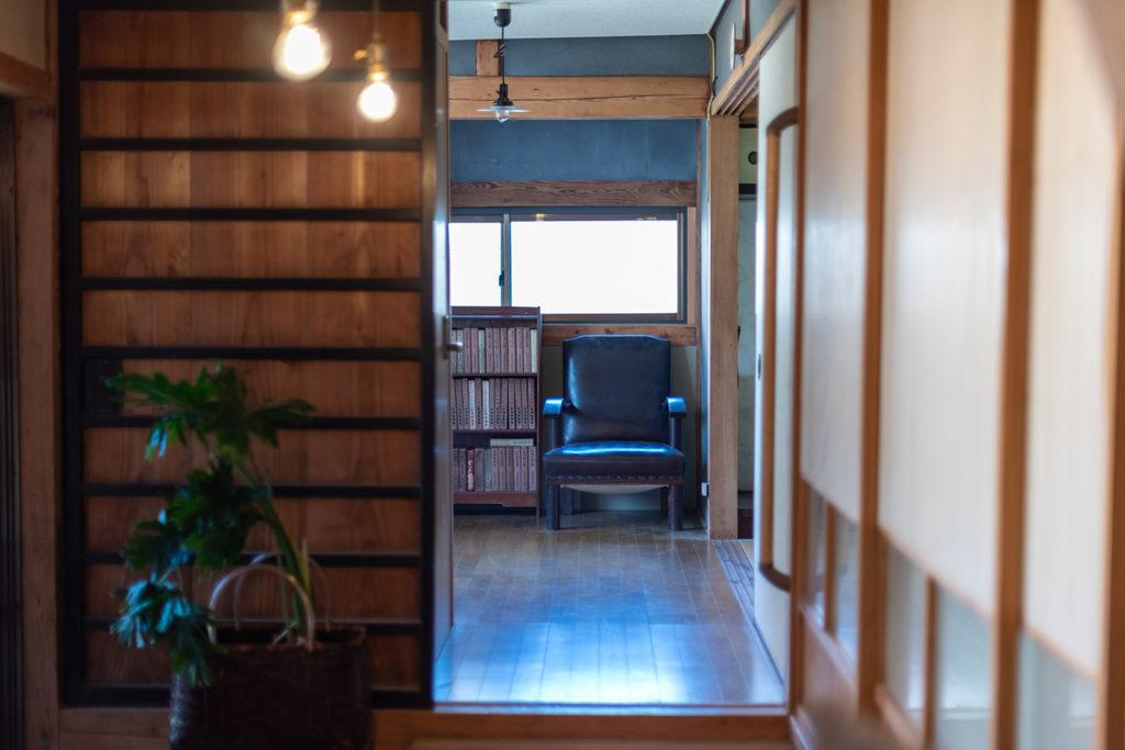 写真:木の引き戸と障子、廊下。突き当たりに黒いソファと本棚がある。