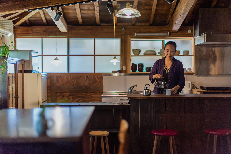 写真:手前にテーブル、奥にキッチンカウンター。キッチンでは女性がコーヒーを淹れている。