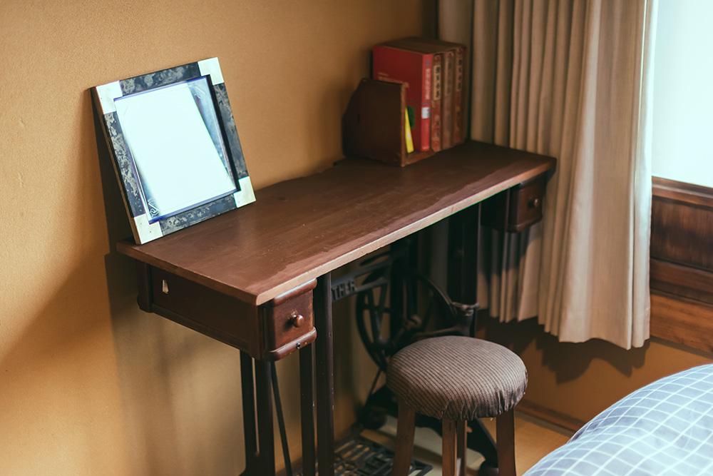 写真:レトロな机と座面の丸い椅子。机には写真立てと本が数冊置いてある。