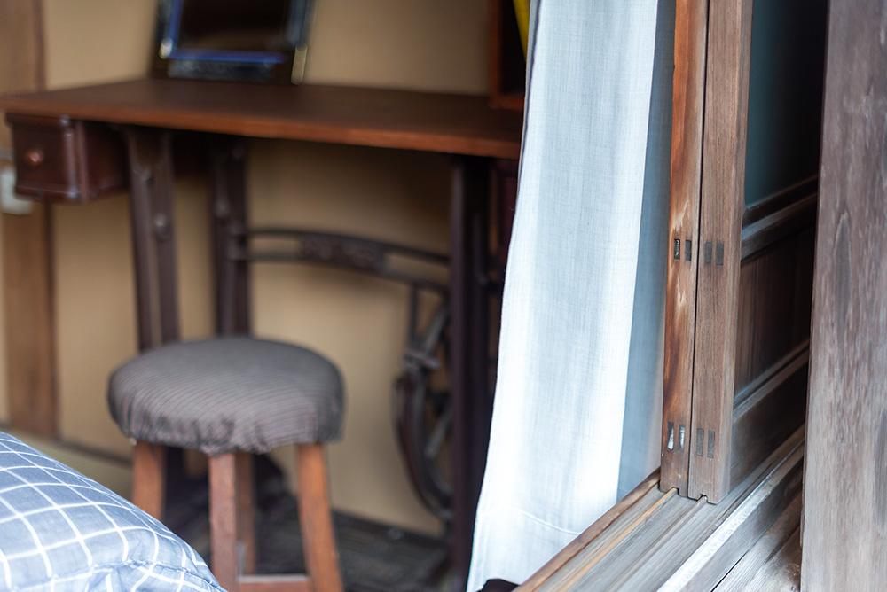 写真:窓の外から部屋をのぞいたところ。白い木綿のカーテンが揺れている。