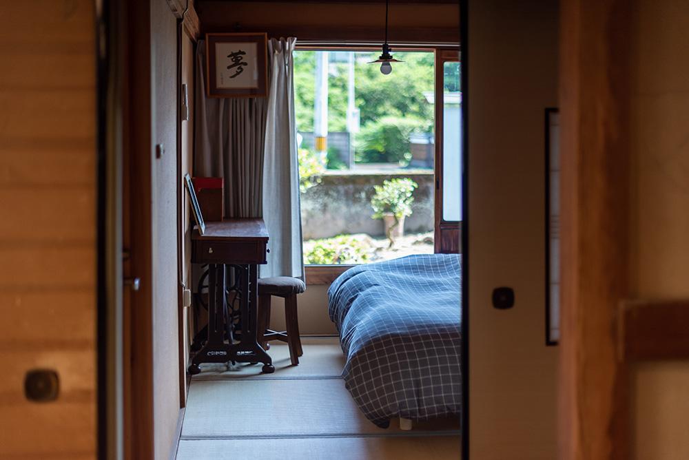 写真:窓際にベッドと机のあるミニマムな和室。