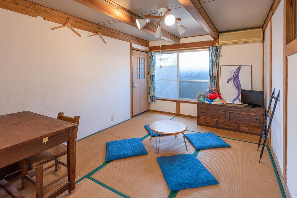 写真:中央に折りたたみ式の小さな丸いちゃぶ台がある和室。青い座布団が4枚並べてある。