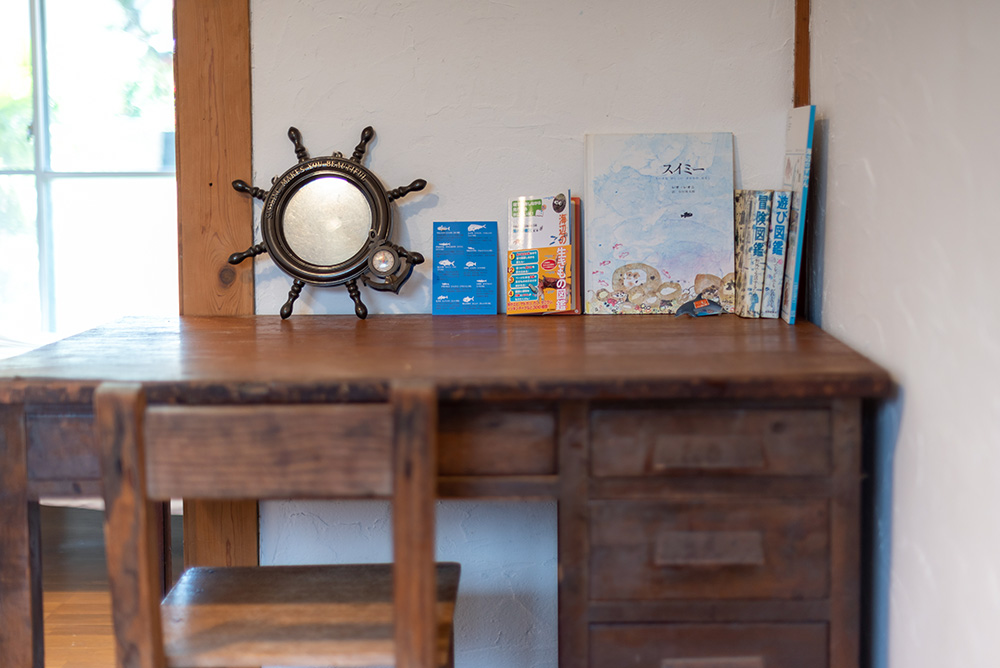 写真:木製の机。絵本「スイミー」や船の舵のミニチュアなど、海グッズが置いてある