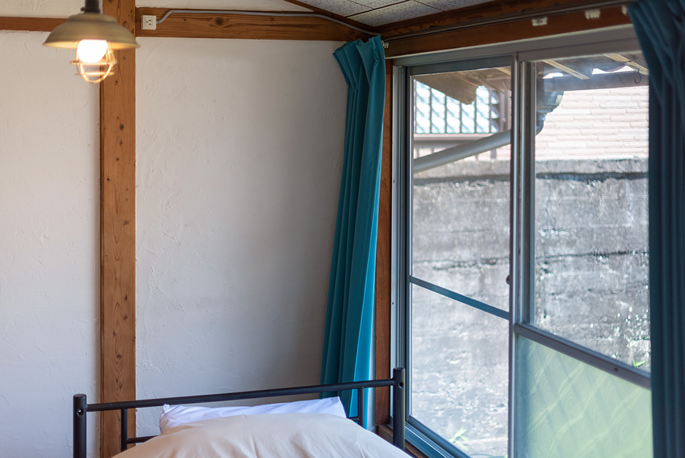 写真:窓際に置かれたベッド。カーテンはターコイズブルー
