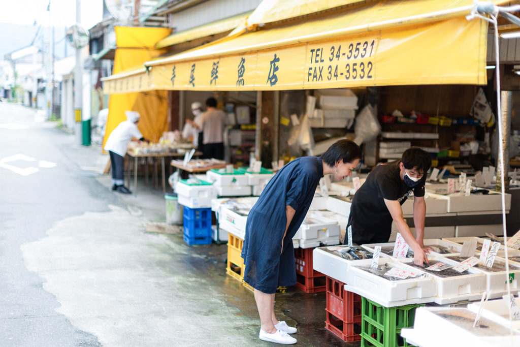写真:魚屋の店頭に並んだ魚を覗き込む女性。店員の男性が説明をしている。