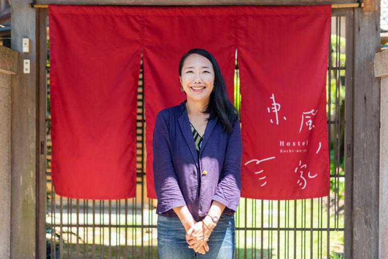 写真:赤いのれんの前に笑顔で立っている黒髪の女性。のれんには「東風ノ家」のロゴ。
