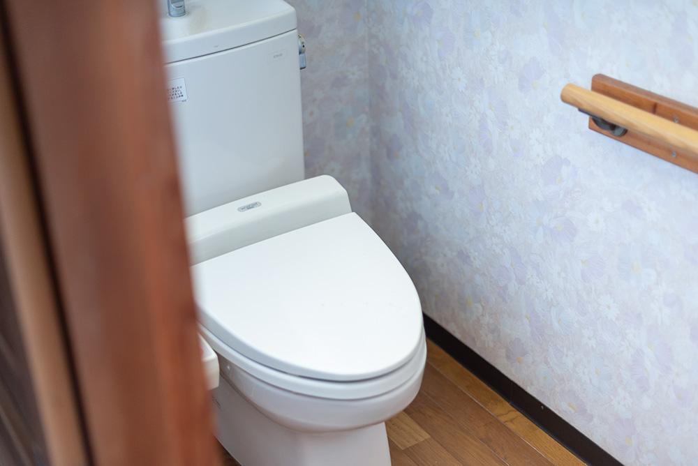 写真:ウォシュレット付きの洋式トイレ。壁には手すりがついている。