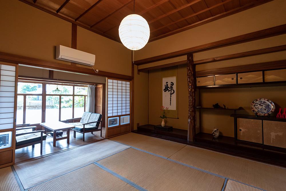 写真:縁側と床の間のある和室。縁側にはテーブルとソファがあり、庭を眺められる。