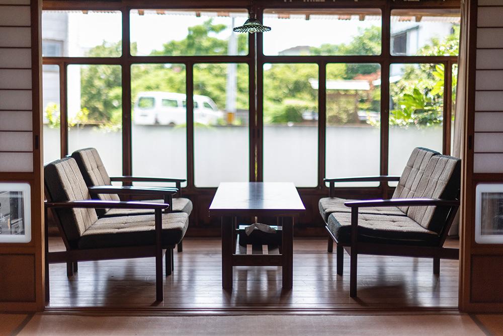 写真:テーブルとソファのある縁側。ソファは2席と3シートが机を挟んで向かい合っている。窓の向こうに庭の緑が見える。