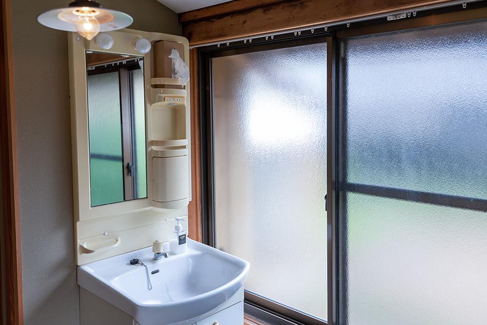 写真:鏡付きの洗面台。側には大きな窓がある。