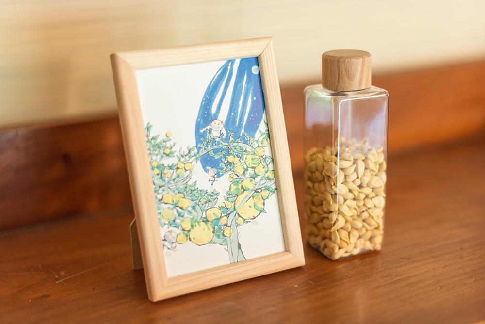 写真:ゆずのタネがたくさん入った小瓶と、ゆずの木の絵葉書