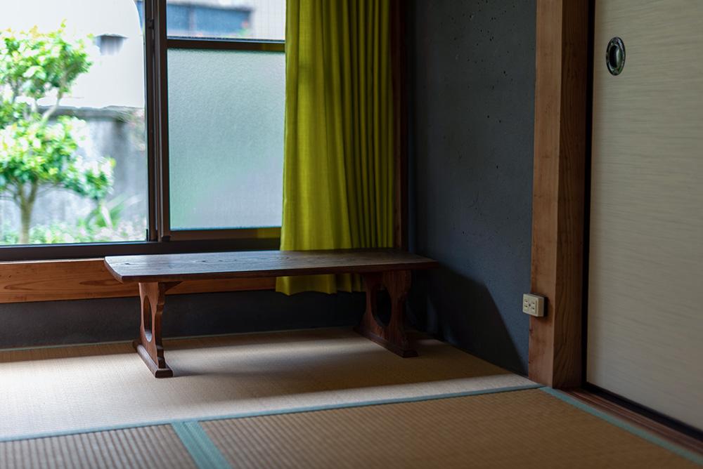 写真:窓辺に置かれた文机。窓には黄緑色のカーテンがかかっている。